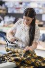 Молодая швея гладильная куртка в мастерской — стоковое фото