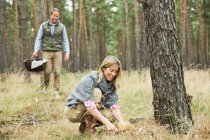 Mid adult couple foraging for mushrooms in forest — Stock Photo