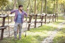 Giovane coltivatore maschio che si appoggia contro la rete fissa del paddock, Premosello, Verbania, Piemonte, Italia — Foto stock
