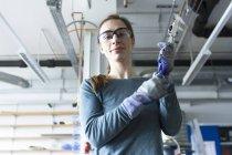 Inquadratura dal basso della donna in laboratorio indossare sicurezza occhiali portautensile — Foto stock