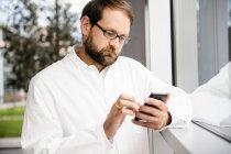 Врач с помощью мобильного телефона у окна — стоковое фото