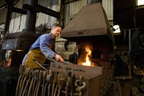 Male caucasian blacksmith at work in workshop — Stock Photo