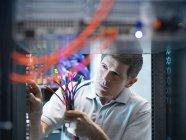 Людина інспектування кабелів і роз'ємів в комп'ютерному серверній кімнаті — стокове фото
