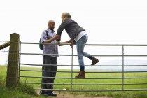Couple escalade la porte dans le champ de campagne — Photo de stock