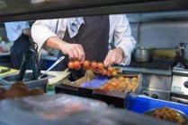 Шеф-повар готовит помидоры в традиционном итальянском ресторане кухни, закрыть — стоковое фото