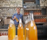 Man with bottles of organic cider — Stock Photo