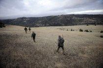 Quatro caçadores de veados caminhando pelo campo, John Day, Oregon, EUA — Fotografia de Stock