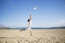 Menino pulando e jogando chapéu no ar na praia — Fotografia de Stock