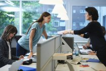 Businesswomen passing paperwork across screen partition in office — Stock Photo