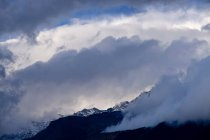 Clouds over snowy mountainside — Stock Photo