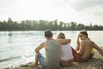 Four young friends sitting on lakeshore — Stock Photo