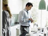 Homme d'affaires mature vérifier le temps dans la cuisine — Photo de stock