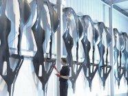 Ingénieur inspectant les carrosseries en fibre de carbone dans une usine de voitures de course — Photo de stock
