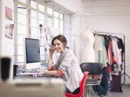 Fashion designer working at computer in fashion design studio, portrait — Stock Photo