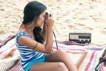 Женщина сидит на пляже и использует камеру — стоковое фото