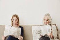 Senior und Mitte Erwachsene Frauen, die Zeitung zu lesen — Stockfoto