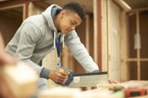 Studente di college maschile utilizzando sega in laboratorio di lavorazione del legno — Foto stock