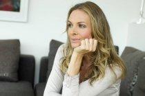 Une femme blonde mature avec une main sur le menton, portrait — Photo de stock