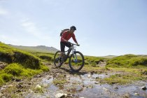 Cyclists cycling through water — Stock Photo