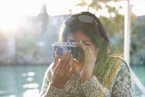 Зрелая женщина-туристка фотографирует на реке Гуадалкивир, Севилья, Испания — стоковое фото