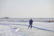 Vista posteriore dell'uomo pattinaggio sul fiume congelato — Foto stock