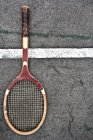 Raqueta de tenis sobre una superficie marcada de pista - foto de stock