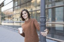 Portrait of mid adult woman with takeaway cup holding city lamppost — Stock Photo