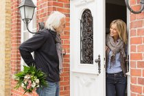 Hombre mayor con ramo, mujer adulta media abriendo la puerta principal - foto de stock