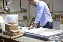 Mann wickelt Rahmen in Luftpolsterfolie auf Tisch in Bilderrahmen-Werkstatt — Stockfoto