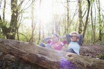 Mulheres na floresta mãos atrás da cabeça fazendo sentar-se contra a árvore caída — Fotografia de Stock
