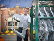 Worker inspecting car parts in car factory — Stock Photo