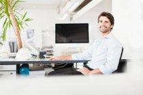 Retrato do empresário sentado na mesa a sorrir — Fotografia de Stock