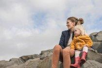 Madre e bambino seduti su pietre — Foto stock