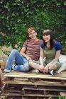 Jovem casal sentado em paletas de madeira — Fotografia de Stock