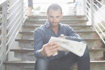 Geschäftsmann liest Zeitung im Treppenhaus — Stockfoto