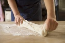 Cropped image of baker stretching bread dough — Stock Photo