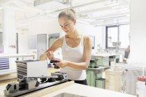 Técnico en taller mecánico dentro de laboratorio óptico - foto de stock