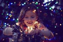 Ragazza circondata da luci avvolgenti regali di Natale a Natale — Foto stock