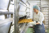 Baker removing tray of baked pastries from oven in bakery — Stock Photo
