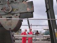 Travailleurs regardant vers le haut à côté d'une pompe à huile au-dessus d'un puits de pétrole terrestre (hochant la tête âne / pompage ) — Photo de stock
