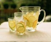 Кувшин для лимонада и бокалы на столе со свежими фруктами — стоковое фото