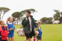 Тренер, несущий футбольные мячи на поле — стоковое фото
