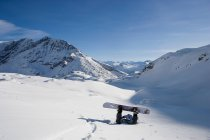 Fallen male snowboarder lying face down — Stock Photo