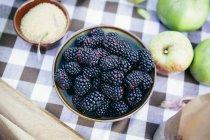 Schüssel mit frisch gepflückten Brombeeren auf Tisch — Stockfoto
