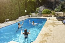 Femme mûre lancer ballon avec fils et fille dans la piscine — Photo de stock