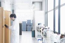 Scientifique lisant l'étiquette du bocal en laboratoire — Photo de stock