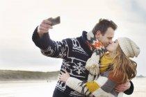 Mediados de pareja adulta tomando autorretrato con teléfono inteligente en la playa, Bloemendaal aan Zee, Países Bajos - foto de stock