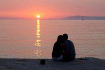 Пара отдыхающих на пирсе на закате — стоковое фото