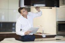 Metà uomo adulto ispezionare cappa aspirante in cucina showroom — Foto stock