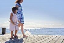 Мать и дочь на пирсе с рыболовной сетью — стоковое фото